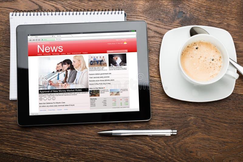 Taza de té y tableta de Digitaces con noticias de negocio foto de archivo libre de regalías