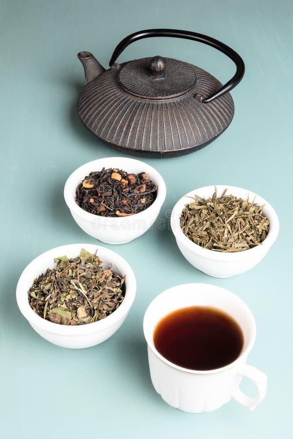 Taza de té y tetera con diverso té tres fotografía de archivo