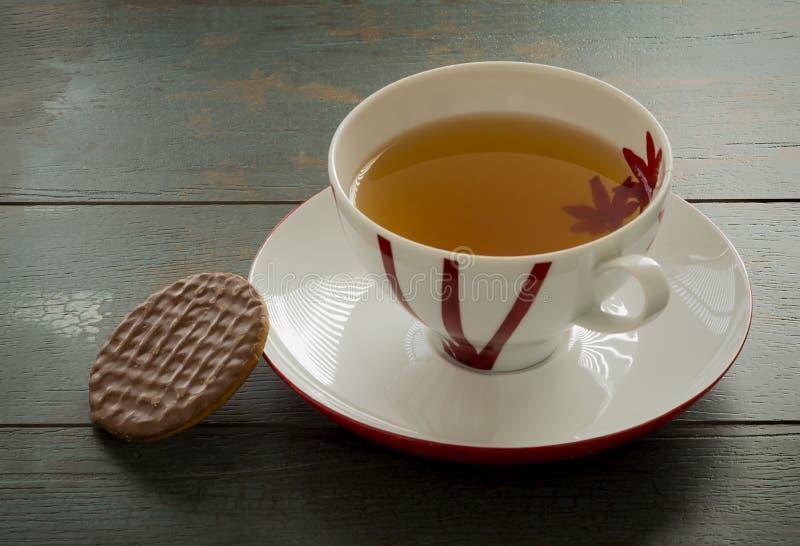 Taza de té y de una galleta imagenes de archivo