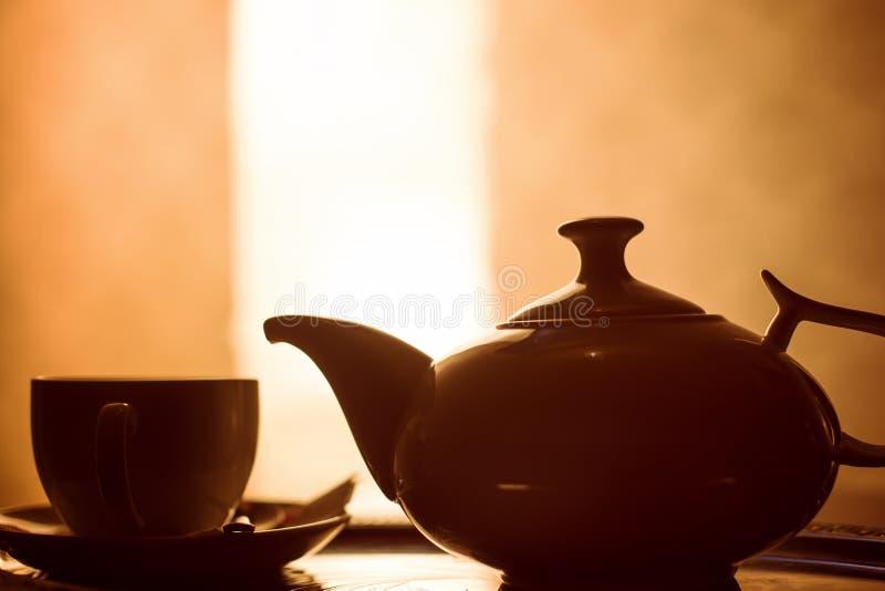 Taza de té y una tetera en una tabla fotografía de archivo libre de regalías