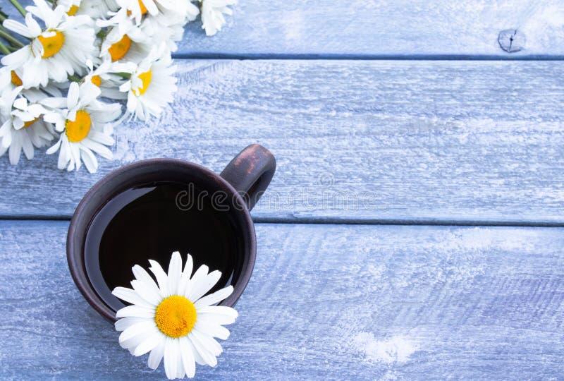 Taza de t? de manzanilla con un ramo de margaritas en un fondo azul de madera imágenes de archivo libres de regalías