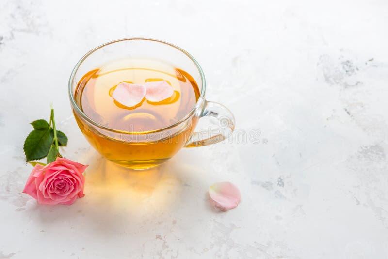 Taza de t? y rosas rosadas blandas en un espacio blanco de la copia del fondo imagen de archivo libre de regalías