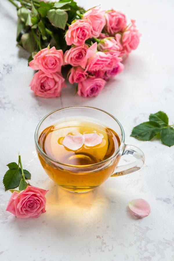 Taza de t? y rosas rosadas blandas en un fondo blanco imagenes de archivo