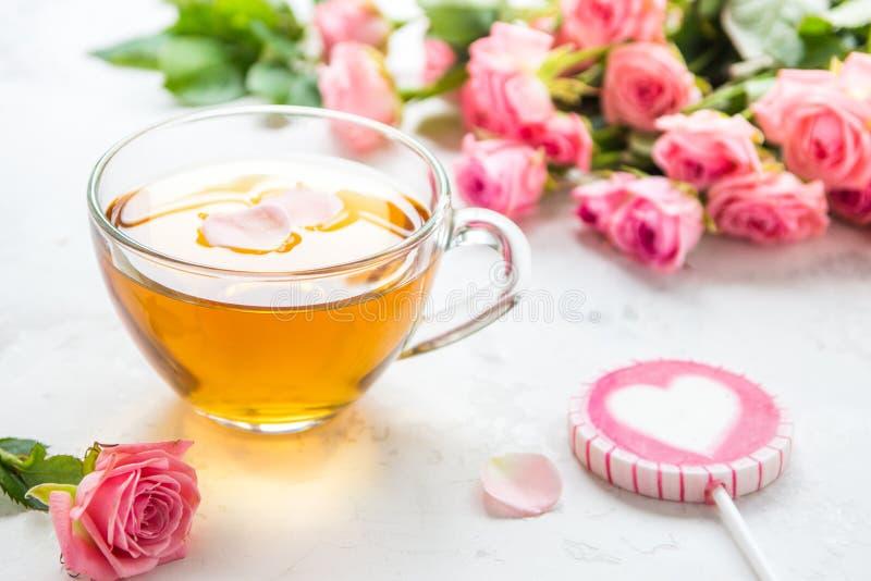 Taza de t? y rosas rosadas blandas en un fondo blanco fotos de archivo libres de regalías