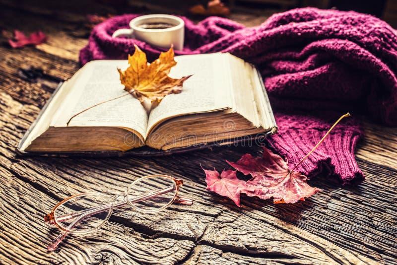 Taza de vidrios del libro viejo del café y de hojas de otoño imagenes de archivo