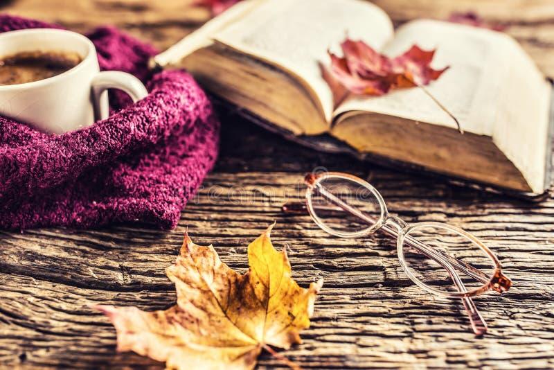 Taza de vidrios del libro viejo del café y de hojas de otoño fotos de archivo libres de regalías