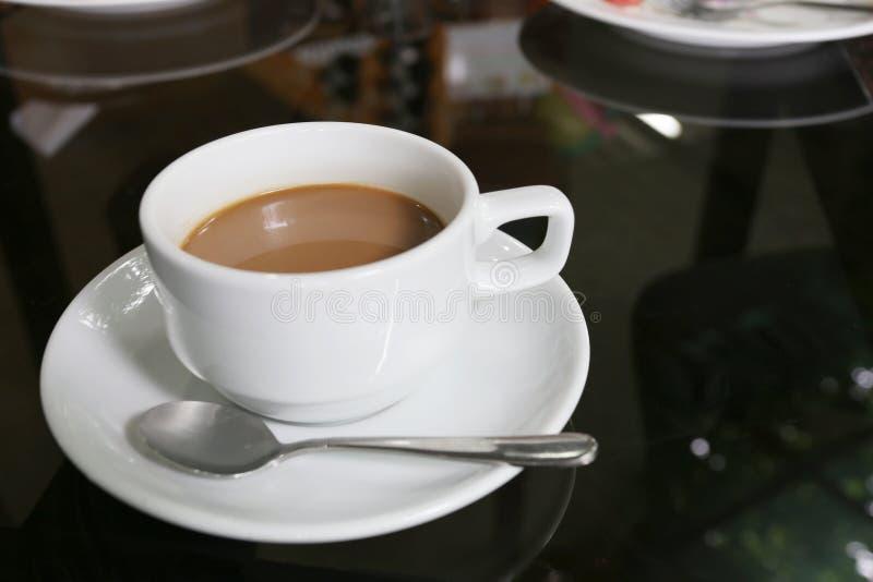 Taza del café con leche colocada en la tabla de las comidas foto de archivo libre de regalías