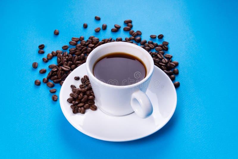 Taza del café express con los granos del café en un fondo azul imagen de archivo