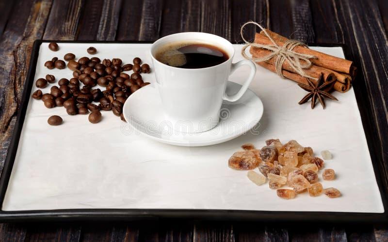 Taza del café express, granos de café, azúcar y canela con anís en un fondo blanco imagen de archivo