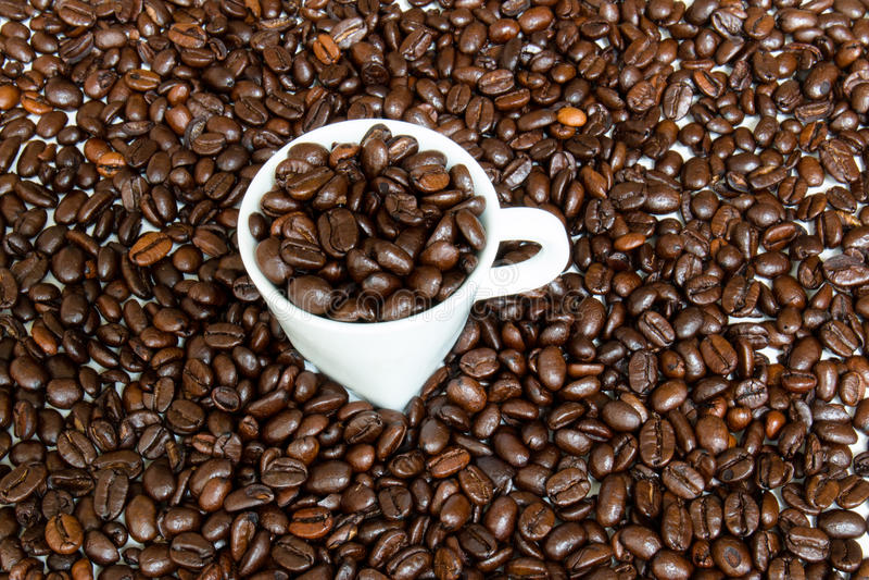 Taza del café express llenada y rodeada por los granos de café imagen de archivo