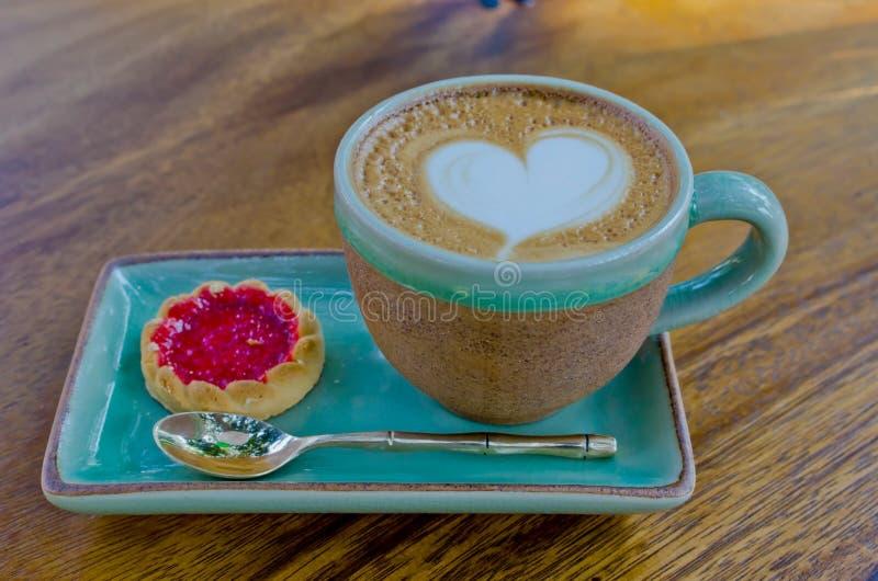 Taza del café, forma del corazón con la galleta de la fresa en el backg de madera imágenes de archivo libres de regalías