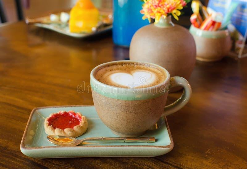 Taza del café, forma del corazón con la galleta de la fresa en la madera imágenes de archivo libres de regalías