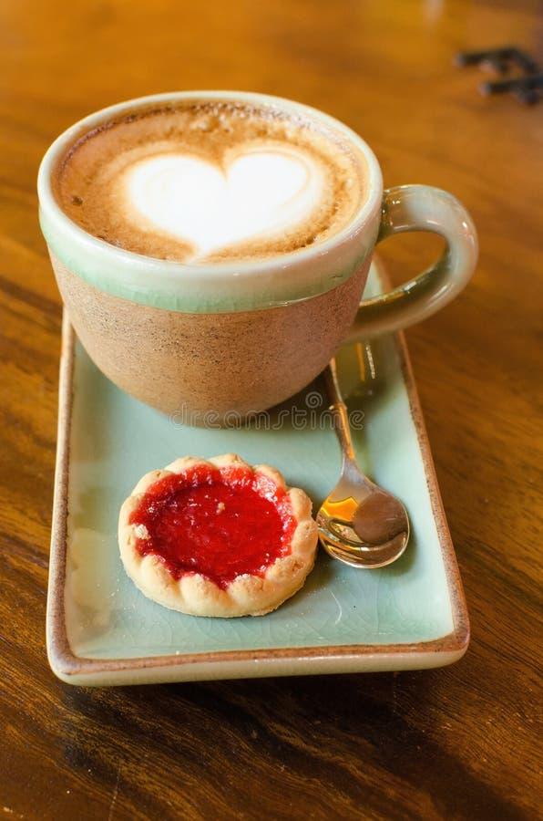 Taza del café, forma del corazón con la galleta de la fresa en la madera fotografía de archivo