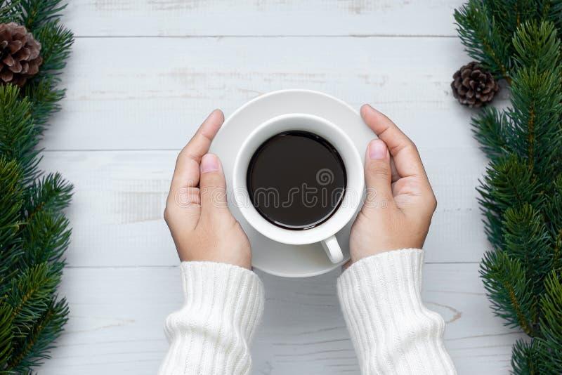 taza del café sólo de la tenencia de la mano de la mujer con la decoración de la Navidad, la Feliz Año Nuevo y Navidad fotos de archivo libres de regalías