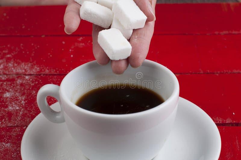 Taza del caf? con leche con los cubos del az?car aislados en un fondo rojo imagenes de archivo