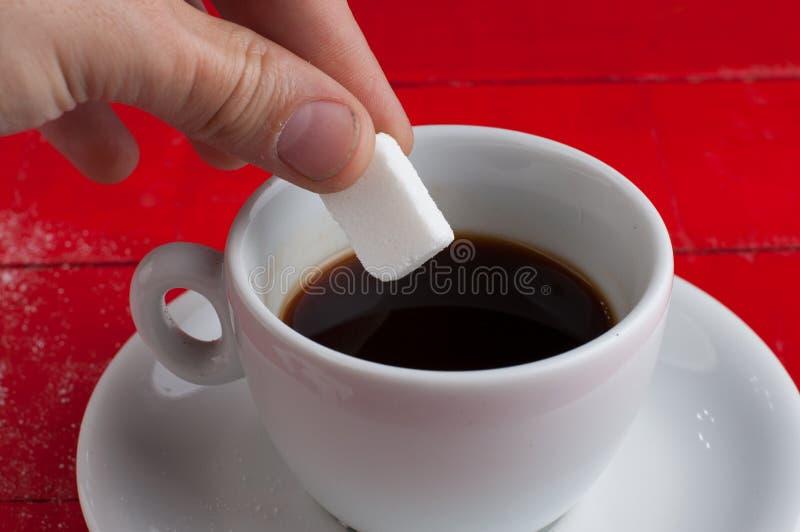 Taza del caf? con leche con los cubos del az?car aislados en un fondo rojo foto de archivo libre de regalías