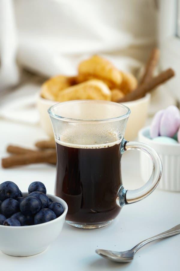 taza del desayuno de la ma?ana de caf?, cruasanes, merengues dulces coloreados, ar?ndanos en un vidrio blanco de la arcilla fotografía de archivo