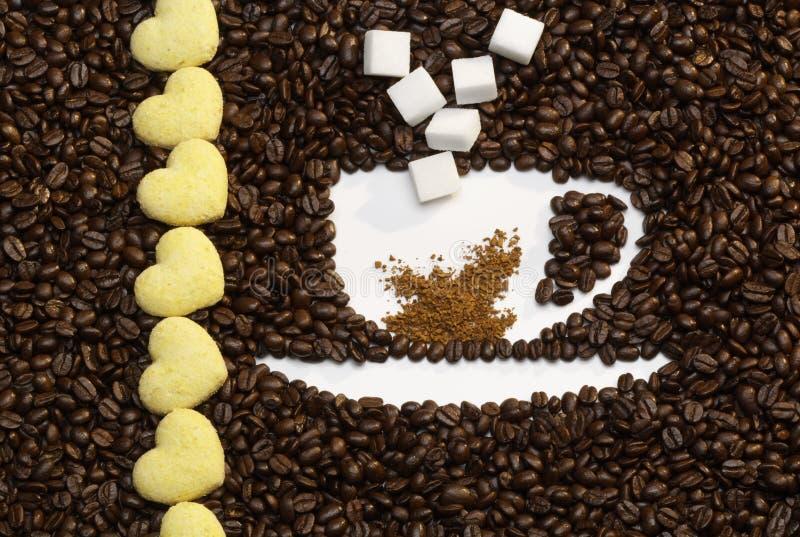 Taza del grano de café con las galletas imagen de archivo
