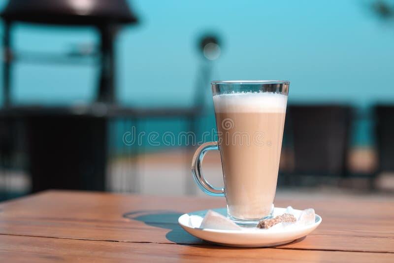 Taza del Latte en una tabla de madera con el azúcar de terrón imagen de archivo