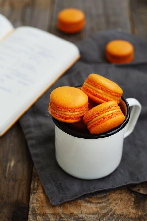 Taza del metal blanco por completo de galletas de color naranja de los macarrones fotos de archivo libres de regalías