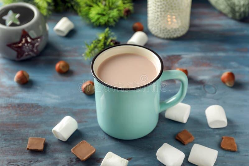 Taza del metal de cacao caliente con las melcochas y el chocolate en la tabla de madera fotografía de archivo libre de regalías