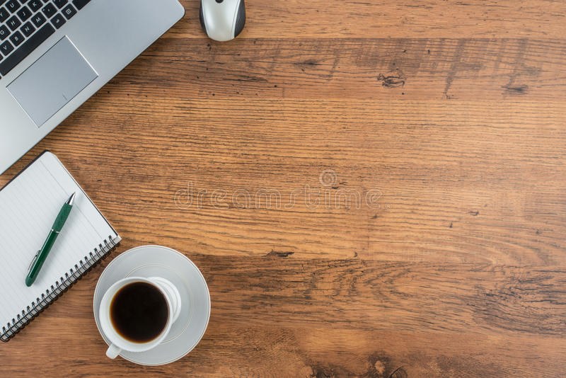 Taza del ordenador portátil, del cuaderno y de café en el escritorio del trabajo imagenes de archivo