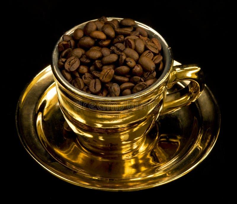 Taza del oro con los granos de café fotos de archivo