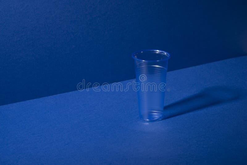 Taza del plástico transparente en fondo azul con el espacio de la copia fotos de archivo