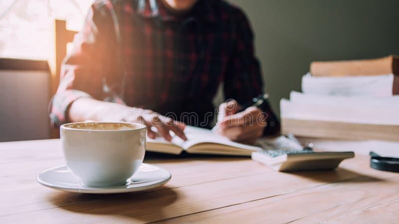 Taza del primer de caf? caliente Hombre asiático en pluma de tenencia de la camisa de tela escocesa que escribe un avance del inf foto de archivo
