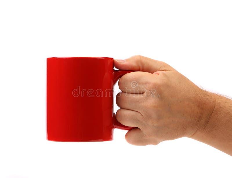 Taza del rojo del asimiento de la mano. imagen de archivo