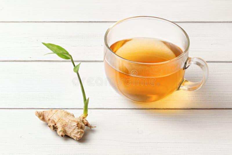 Taza del té ambarino recientemente preparado, mojado de cristal del vapor, ginge seco foto de archivo