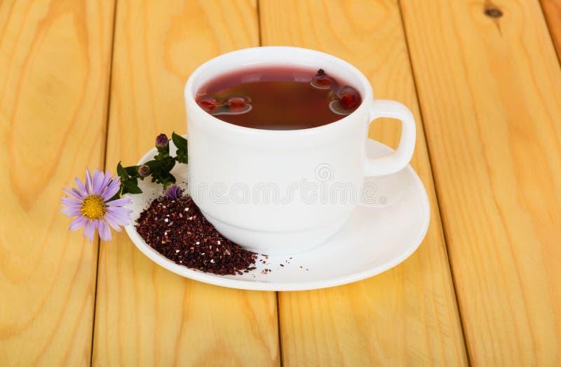 Taza del té caliente, frutas machacadas de la perro-rosa seca en el platillo, contra el fondo de la tabla imágenes de archivo libres de regalías