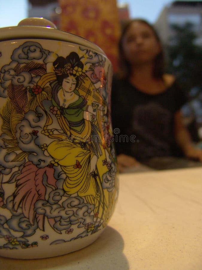 Taza del té con una tapa, con la pintura asiática hermosa en ella y una manija del finger, colocándose en la tabla blanca fotografía de archivo libre de regalías
