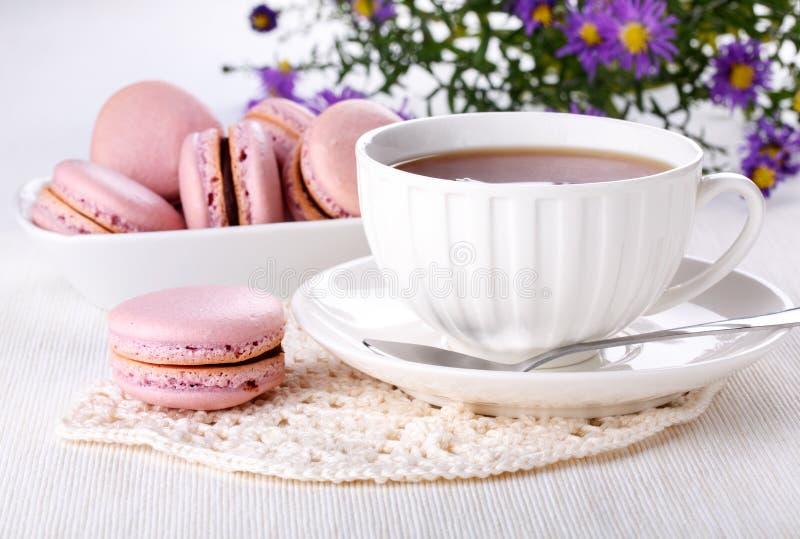 Taza del té y de los macarrones rosados - galletas francesas en la tabla blanca foto de archivo
