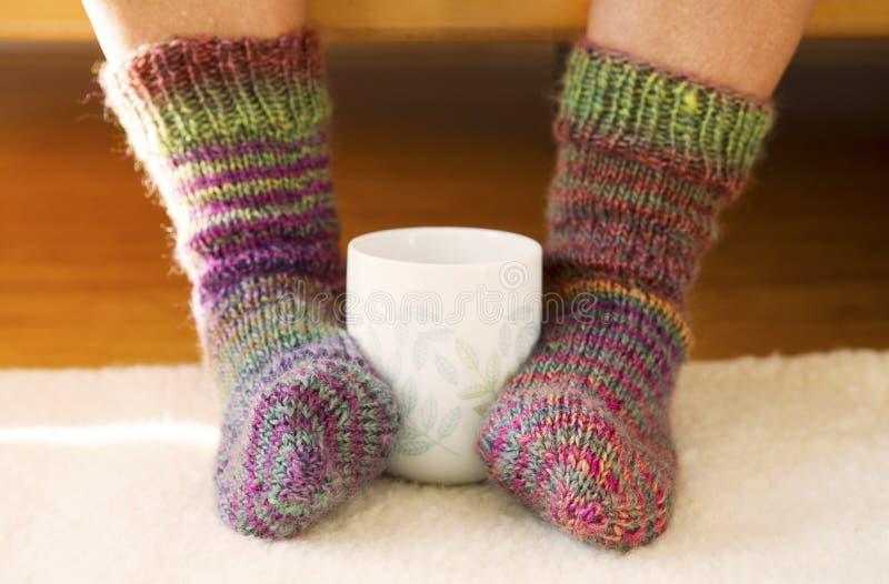 Taza entre dos pies con los calcetines fotos de archivo