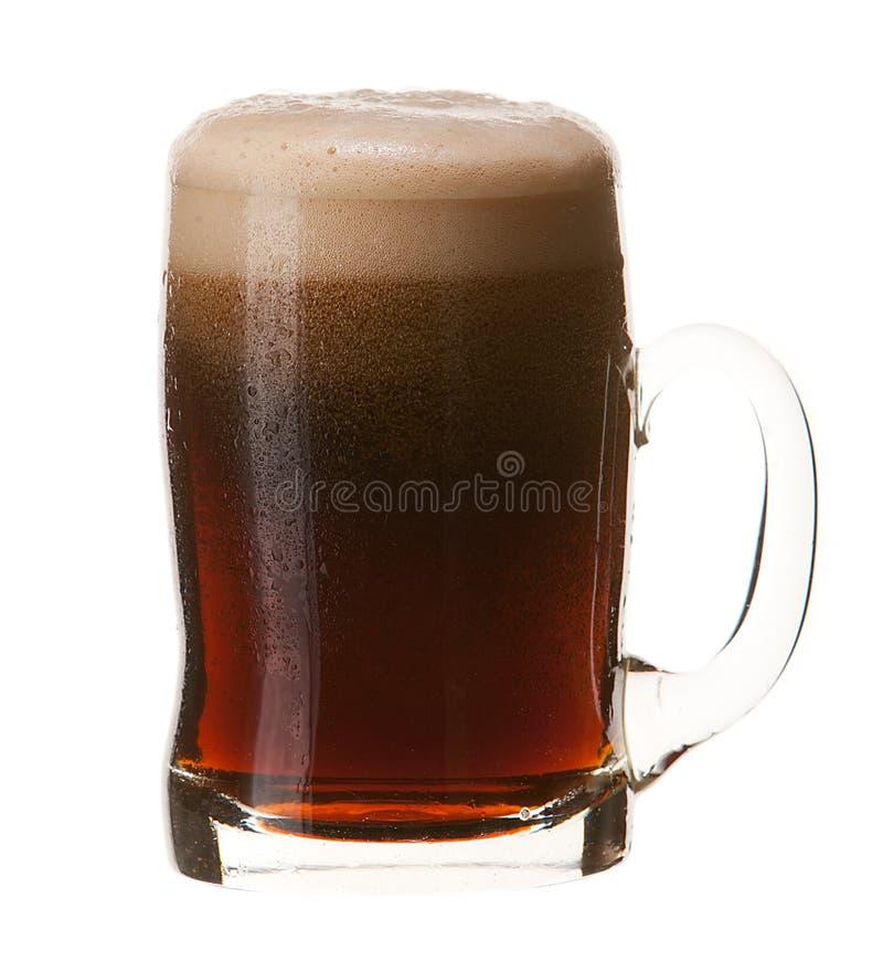 Taza fría de cerveza oscura con la espuma aislada en el fondo blanco fotografía de archivo