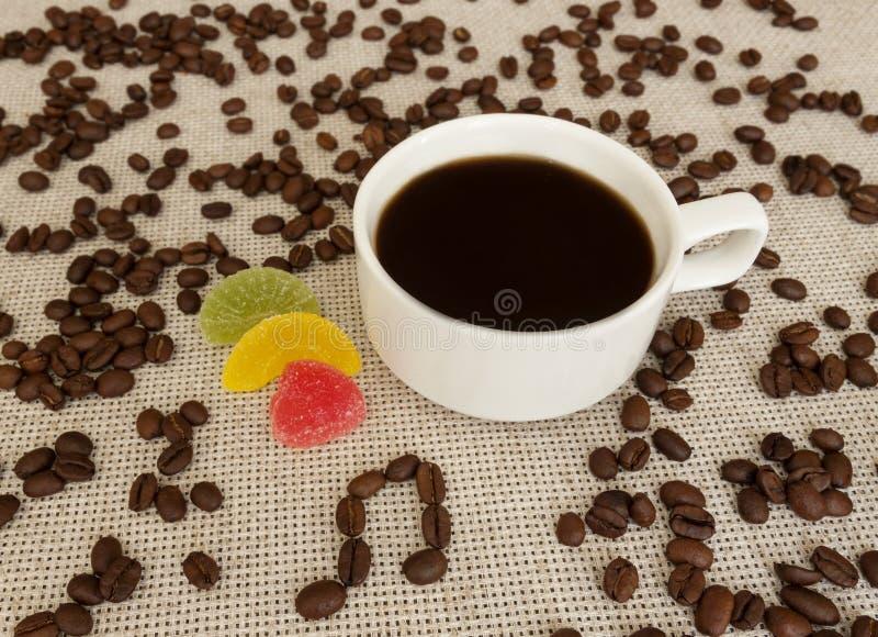 Taza, granos de café, notas musicales y melcocha fotografía de archivo libre de regalías