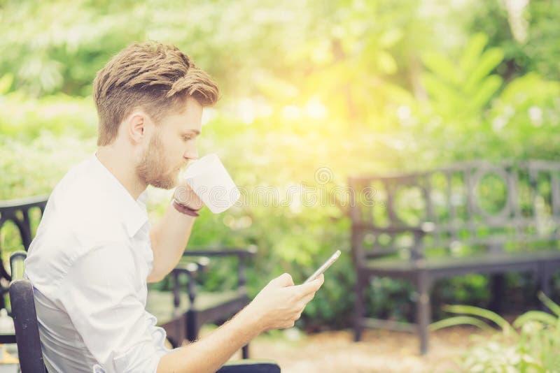 Taza hermosa joven de la bebida del hombre del negocio de café usando el teléfono móvil fotografía de archivo