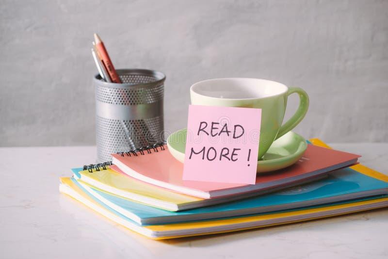 Taza, los cuadernos y etiqueta engomada verdes con el texto - lea más en fondo ligero imagen de archivo libre de regalías