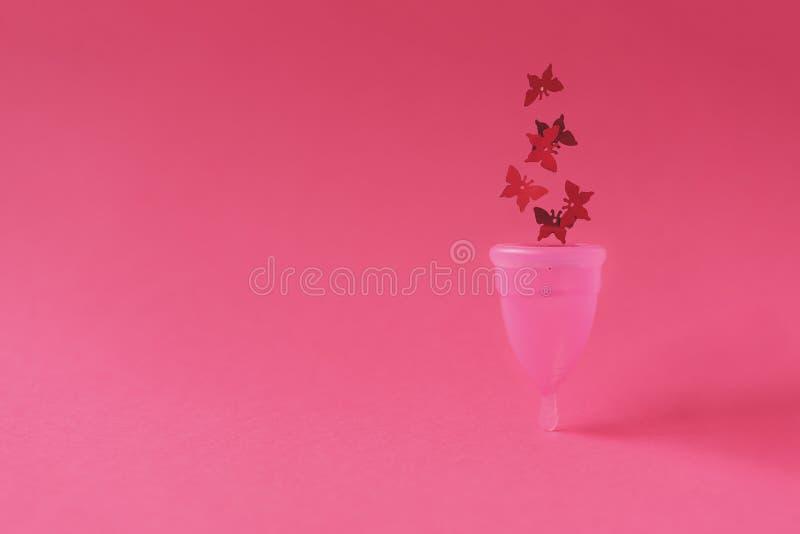 Taza menstrual rosada con brillos rojos en forma de la mariposa en fondo rosado Concepto íntimo femenino de la higiene Front View imagenes de archivo