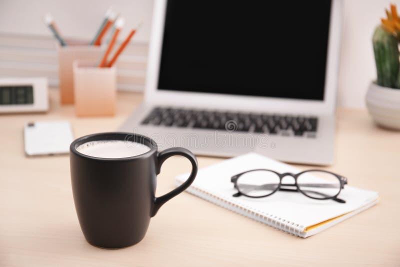 Taza negra con café, los vidrios y el cuaderno en la tabla de la oficina fotografía de archivo