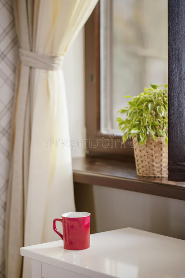 Taza para el café contra una ventana imagenes de archivo