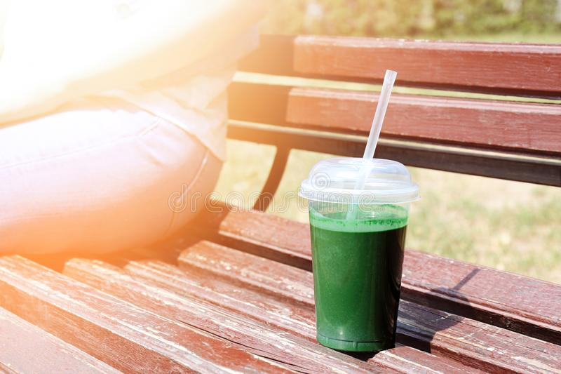 Taza plástica con el smoothie verde fresco en banco de madera foto de archivo