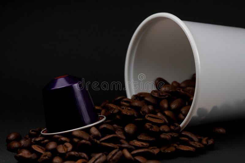 Taza plástica de café con leche que miente, a través de un fondo negro, con los granos de café marrones dentro del vidrio Cafeter imagen de archivo libre de regalías