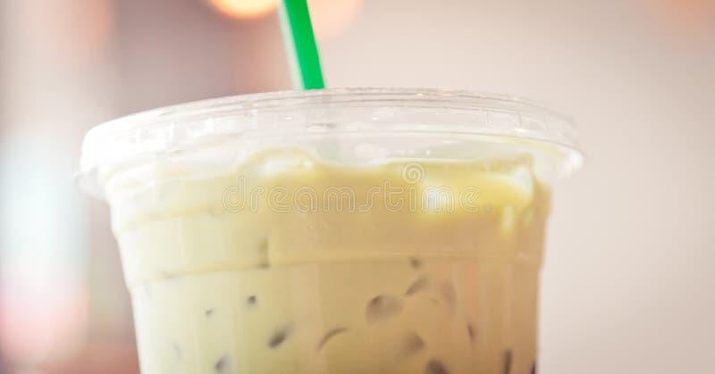 Taza plástica de matcha Iced con la paja verde en tono cremoso imagen de archivo