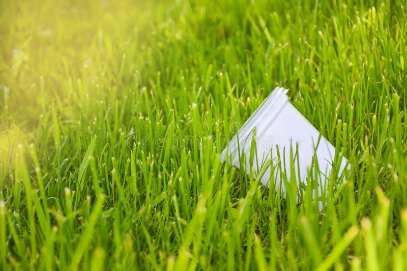 Taza pl?stica en la hierba El concepto de contaminaci?n ambiental, el rechazo de productos pl?sticos, el uso del empaquetado de fotografía de archivo libre de regalías