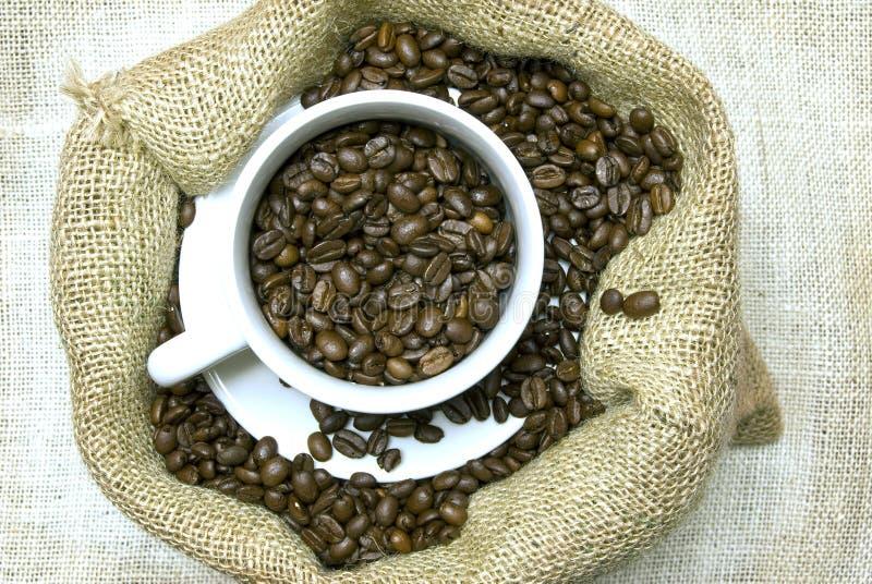Taza por completo de granos de café en bolso de arpillera imagenes de archivo