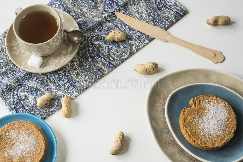 Taza puesta plana de té, de bizcocho tostado con mantequilla de cacahuete y de azúcar fotografía de archivo