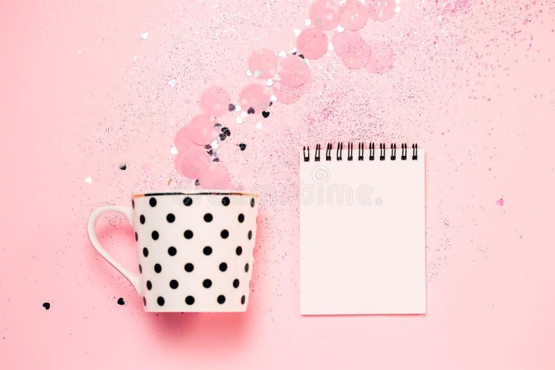 Taza punteada de café y de cuaderno en fondo rosado del confeti fotografía de archivo libre de regalías