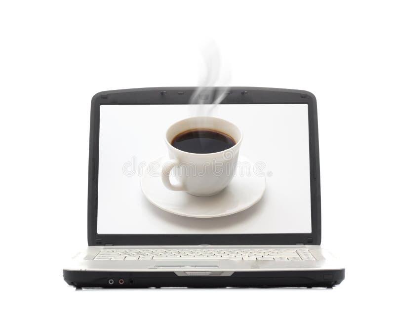 Taza que fuma de café en la pantalla de la computadora portátil fotos de archivo